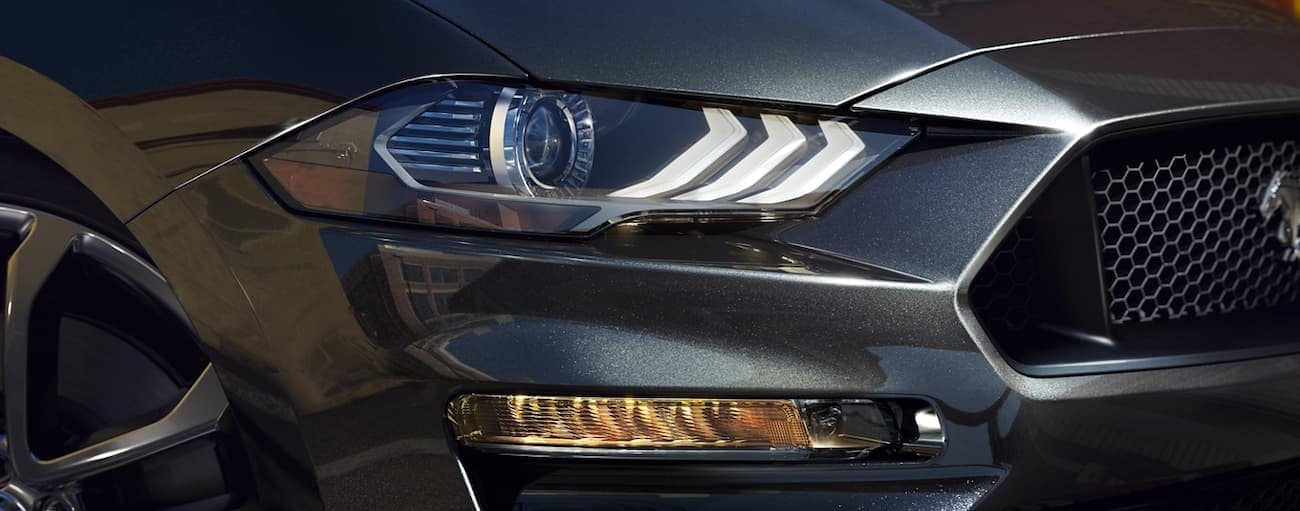 The headlight of a grey 2020 Ford Mustang is shown.