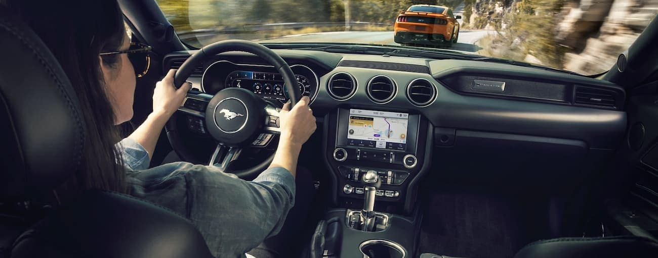 A woman is shown driving form inside her 2020 Ford Mustang.