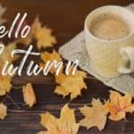 "A coffee cup next to leaves with the saying, ""Hello Autumn."""