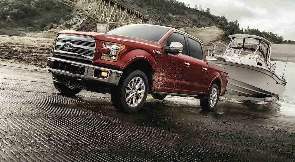 A red 2017 Ford F-150, which wins when comparing the Ford F-150 vs Silverado 1500, is towing a boat out of the water near Cincinnati, OH.