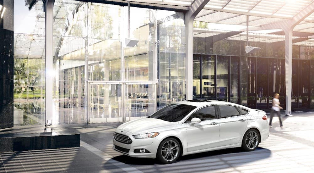 A white 2016 Ford Fusion is parked in front of an office building outside of Cincinnati, OH.