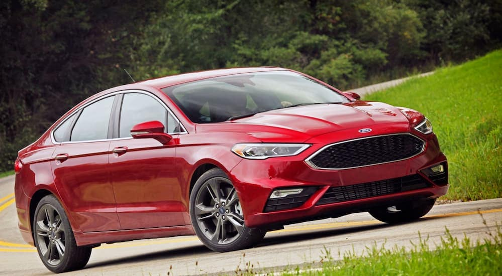 A red 2017 Ford Fusion is driving on a tree-lined road road near Cincinnati, OH.