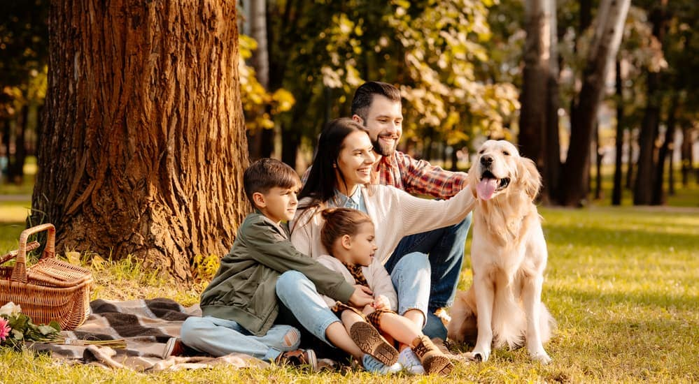 A smiling family and dog are having a picnic near the Mt. Airy Forest in Cincinnati, OH.
