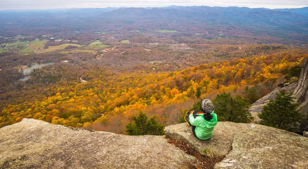 A women is looking over fall colored leaves after hiking in Cincinnati, OH.