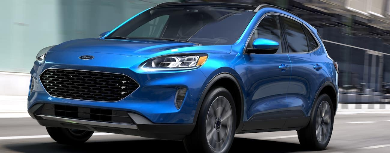 A blue 2020 Ford Escape is driving on a city street near Cincinnati, OH.