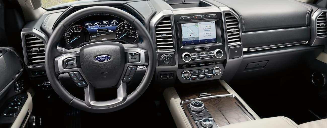 The front tan leather interior of a 2020 Ford Expedition is shown with an infotainment system.