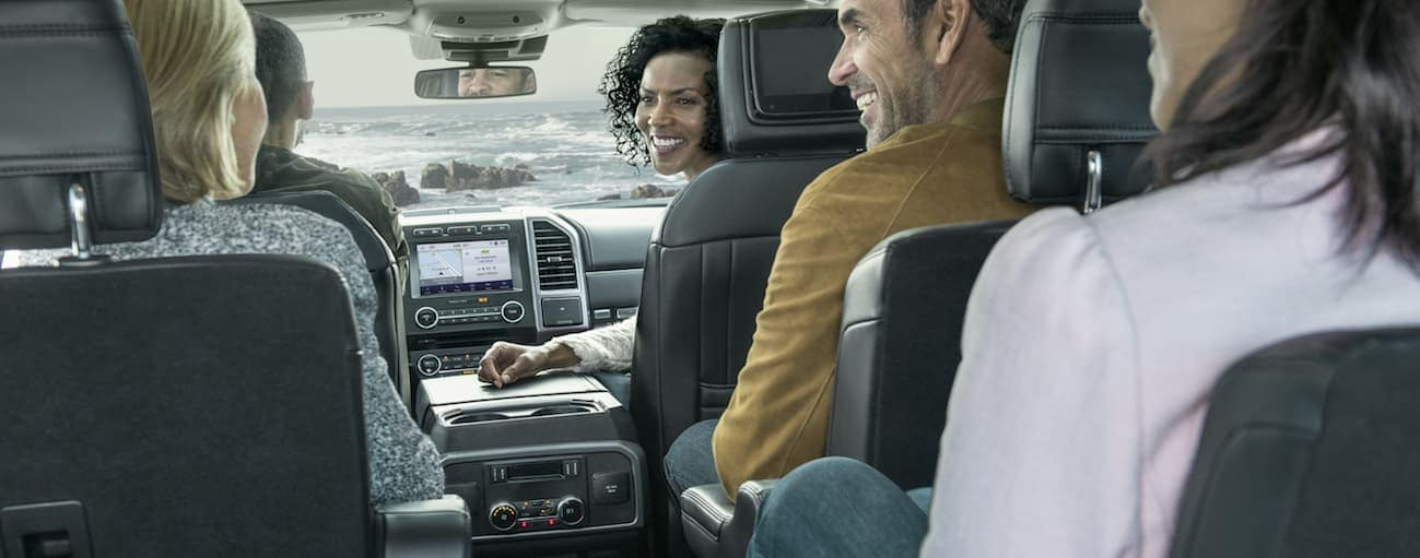 A smiling group of friends are sitting inside of a 2020 Ford Expedition.