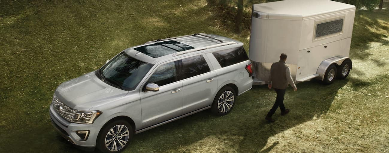 A silver 2020 Ford Expedition is parked in grass while towing a large horse trailer.