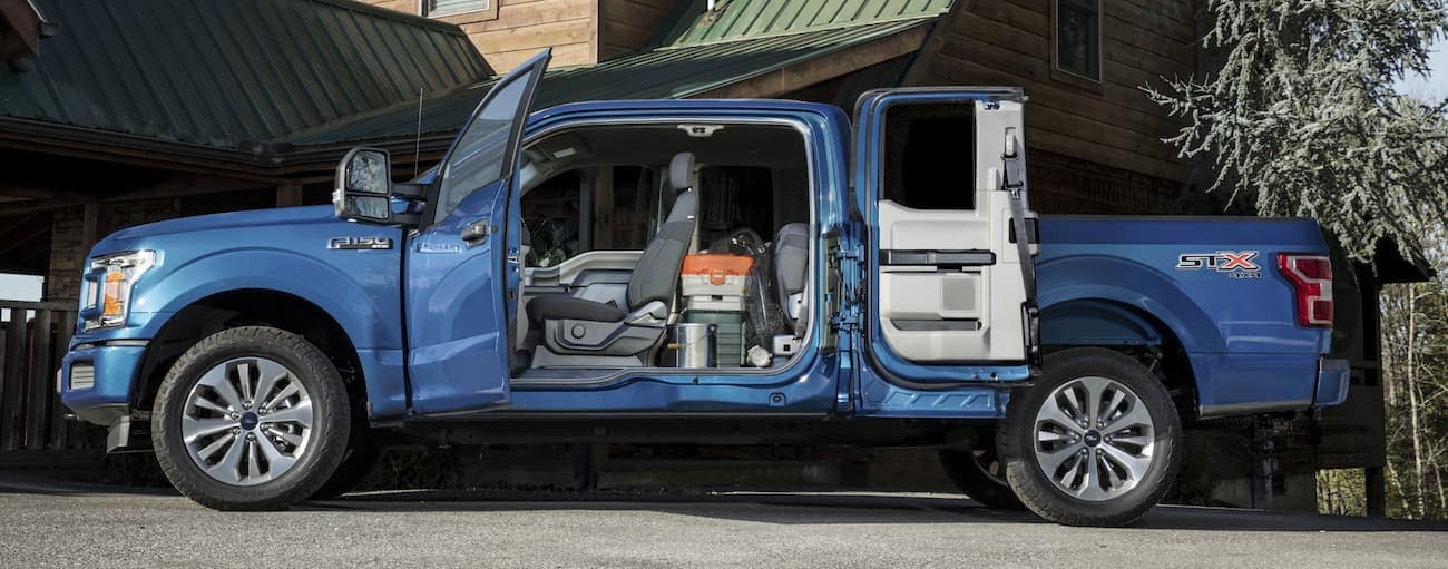 A blue 2020 Ford F-150 is parked in a driveway near Cincinnati, OH with doors open showing the interior.