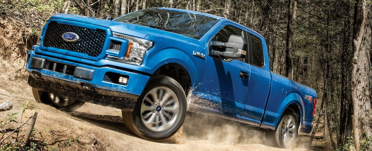 A blue 2020 Ford F-150 is driving on a dirt trail through the woods near Cincinnati, OH.