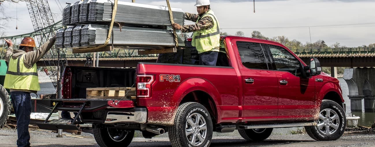 Two workers with yellow vests are putting heavy metal roofing material in the bed of a red 2020 Ford F-150.