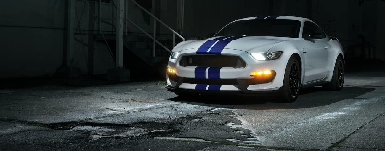 A white 2020 Ford Mustang Shelby GT350 with blue stripes is parked in a dark alleyway with its headlights on.