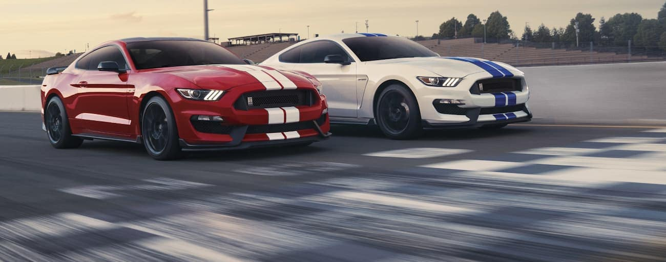 Two 2020 Ford Mustang Shelby GT350s are racing over the finish line on a racetrack near Cincinnati, OH.