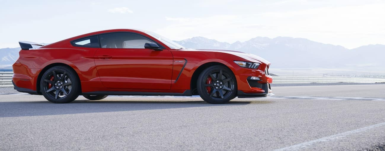 A side view of a red 2020 Ford Mustang Shelby GT350 parked on a track is shown.
