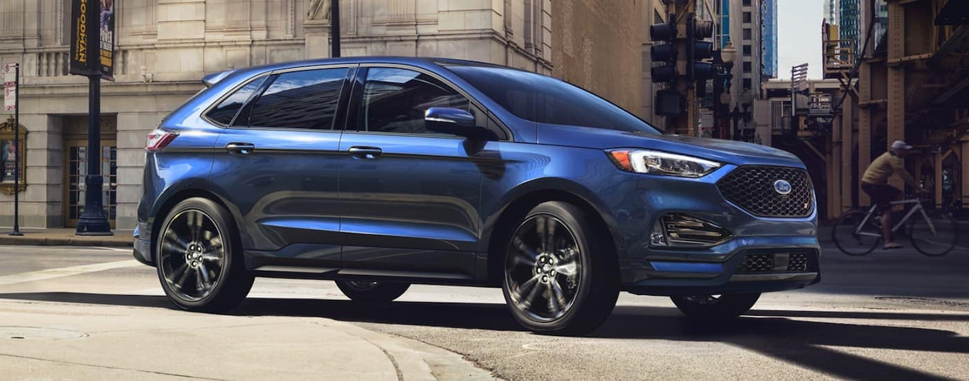 A blue 2020 Ford Edge RS is taking a corner on a city street.