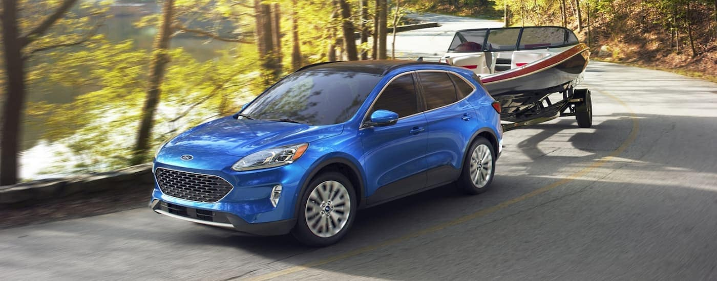A blue 2020 Ford Escape, popular among Ford SUVs, is towing a boat on a winding road.