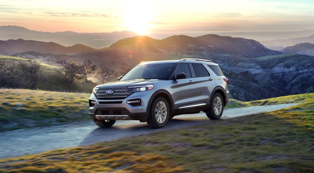 A silver 2020 Ford Explorer is driving with a mountain sunset behind it.
