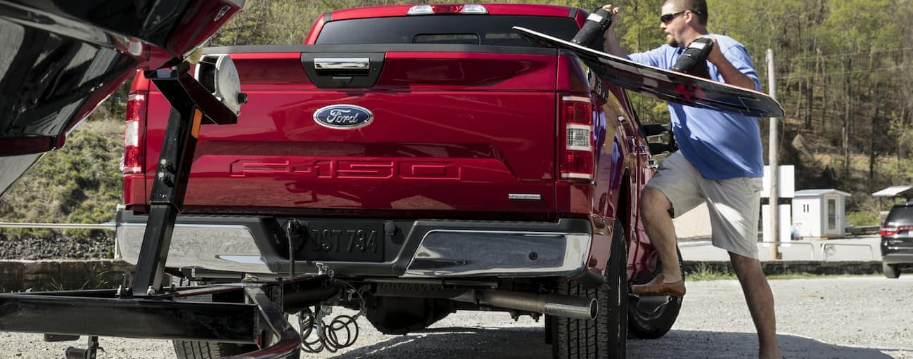 A man is loading boat equipment into the bed of his red 2020 Ford F-150 at a boat yard.