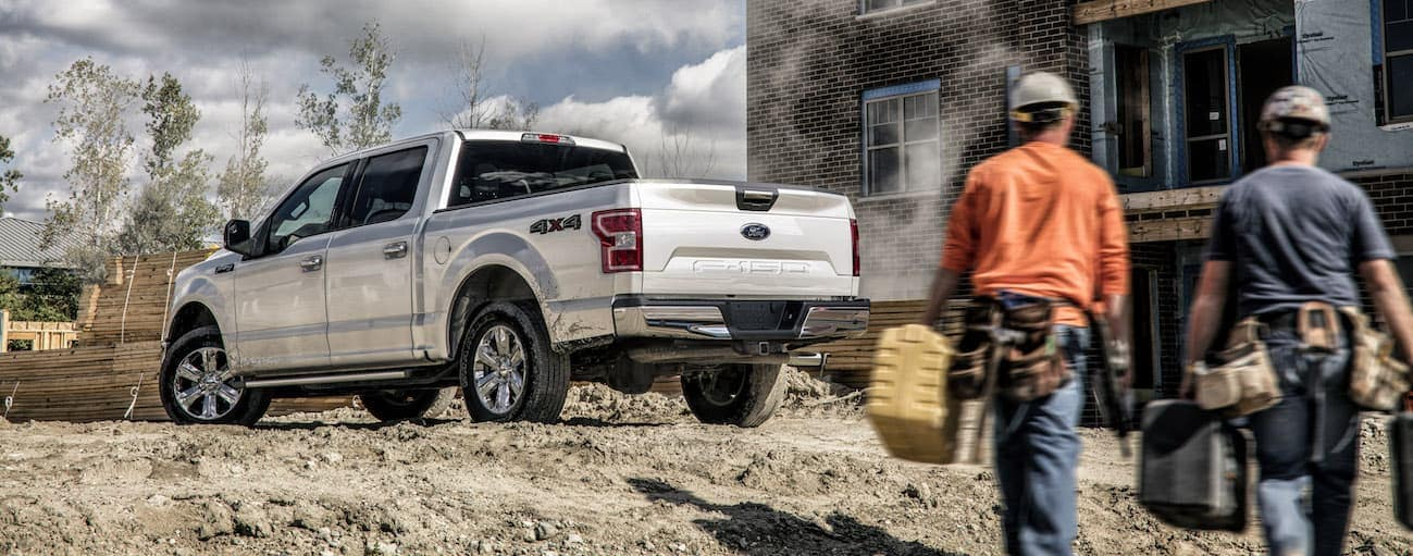 Two Cincinnati, OH construction workers are walking to their silver 2020 Ford F-150.
