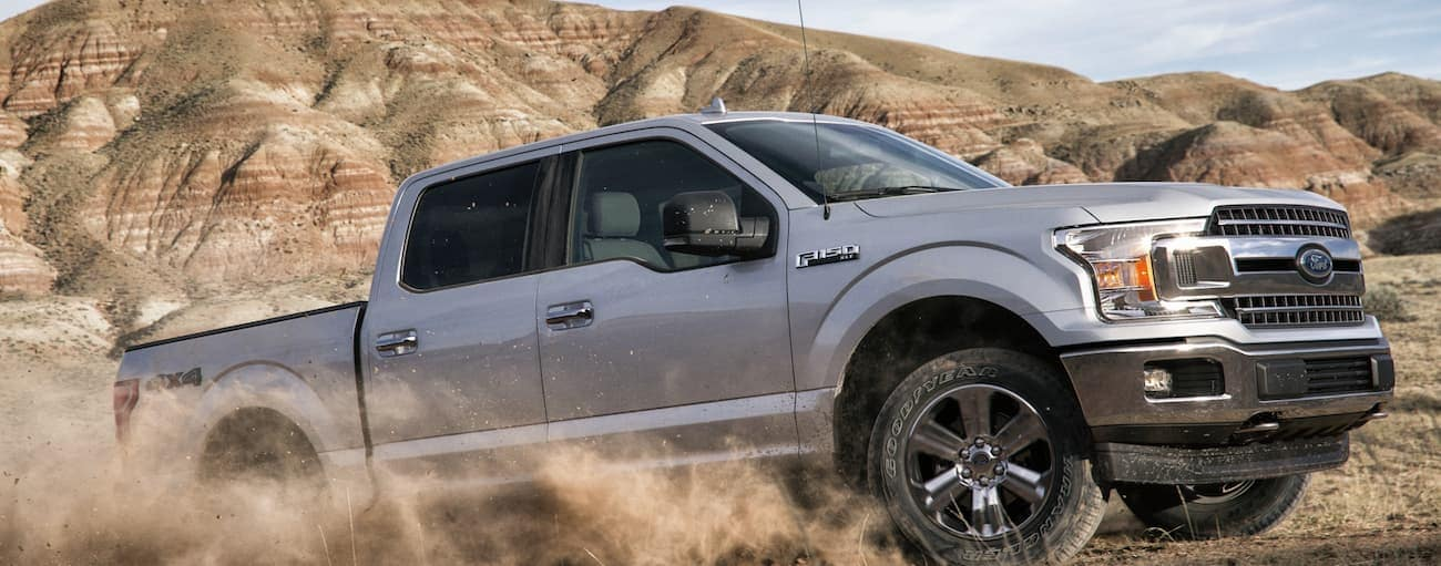 A silver 2020 Ford F-150, which wins when comparing the 2020 Ford F-150 vs 2020 Nissan Titan, is driving through a dirt pit while a dirt cloud rises.
