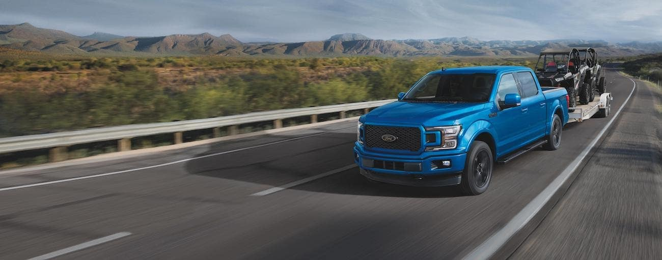 A blue 2020 Ford F-150, which wins when comparing the 2020 Ford F-150 vs 2020 Ram 1500, is towing side by sides on a mountain highway.