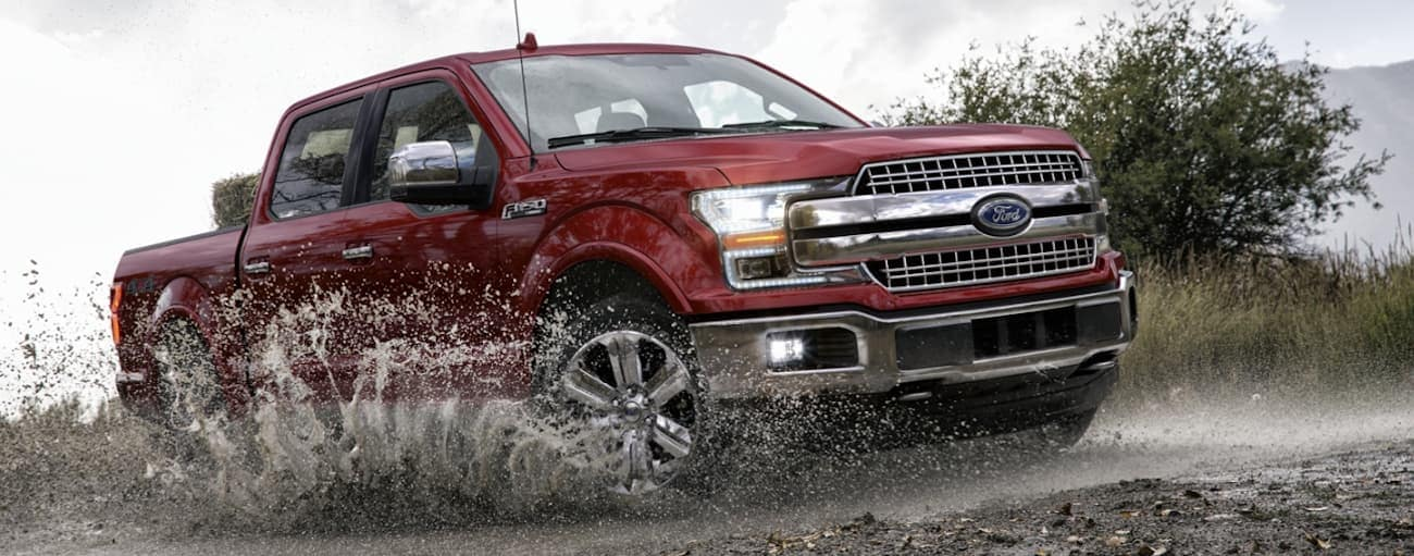 A red 2020 Ford F-150 is driving in the mud near Cincinnati, OH.