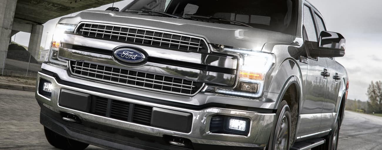 A silver 2020 Ford F-150, which wins when comparing the 2020 Ford F-150 vs 2020 Toyota Tundra, is driving under a bridge near Cincinnati, OH.