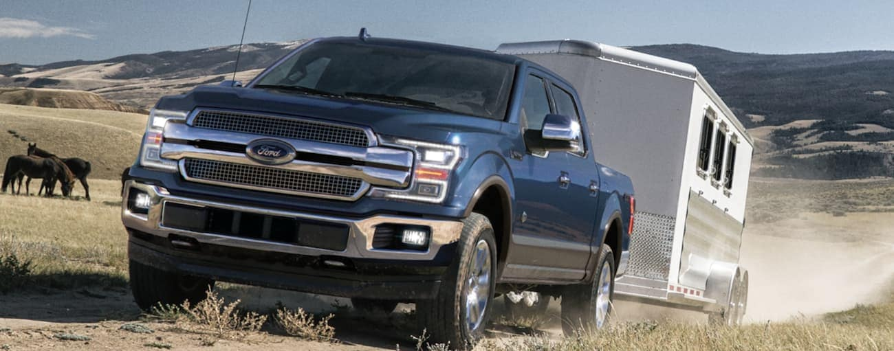 A blue 2020 Ford F-150 is towing a large horse trailer on a farm.