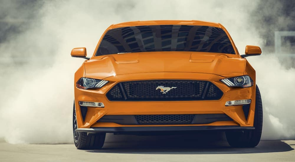 An orange 2020 Ford Mustang is doing donuts in an empoty parking lot with a smoking cloud behind it.