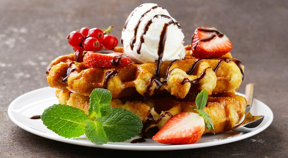 A plate with Belgian waffles, berries, and ice cream is shown.