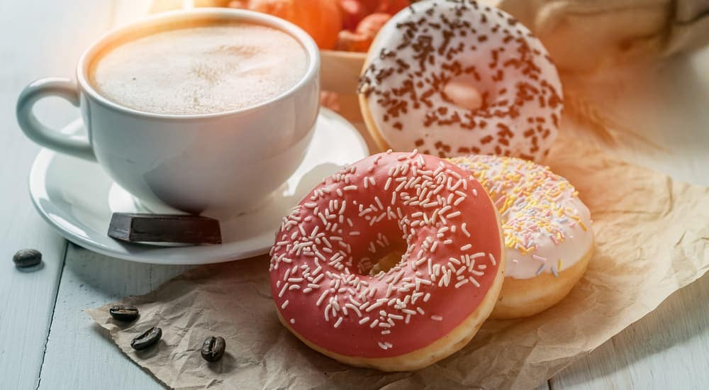 Donuts are next to a mug of coffee at a Cincinnati, OH cafe.