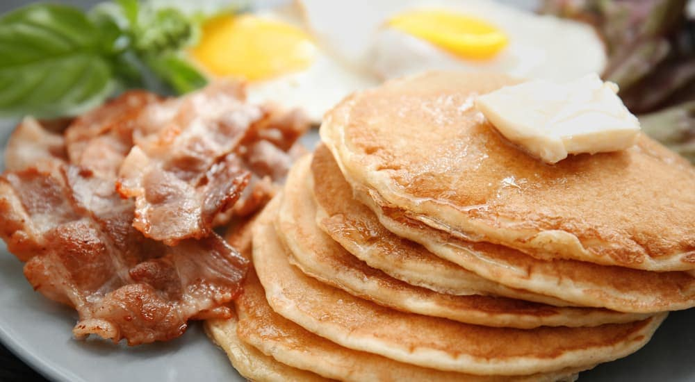 A plate with pancakes, bacon, and eggs is shown.
