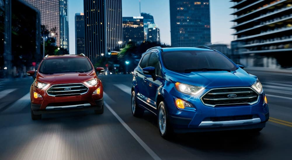 Two Ford SUVs, a red and a blue Ecosport, are driving through Cincinnati, OH, at night.
