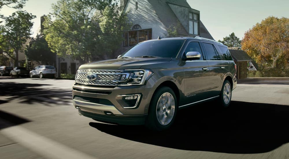 A gold colored 2020 Ford Expedition, one of the largest Ford SUVs, is driving through a suburb.