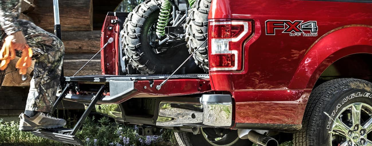A man is using the Tail Gate Assist Step while loading his ATV into the bed of his red 2020 Ford F-150.