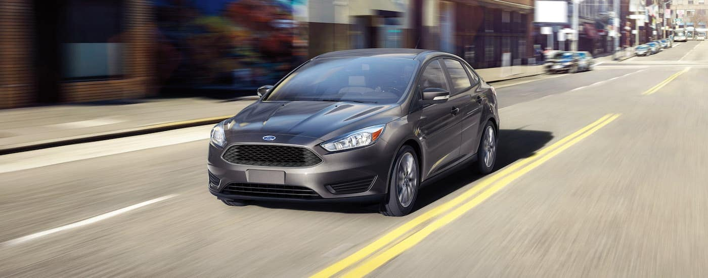 A grey 2016 Ford Focus is driving down a city street in Cincinnati, OH.