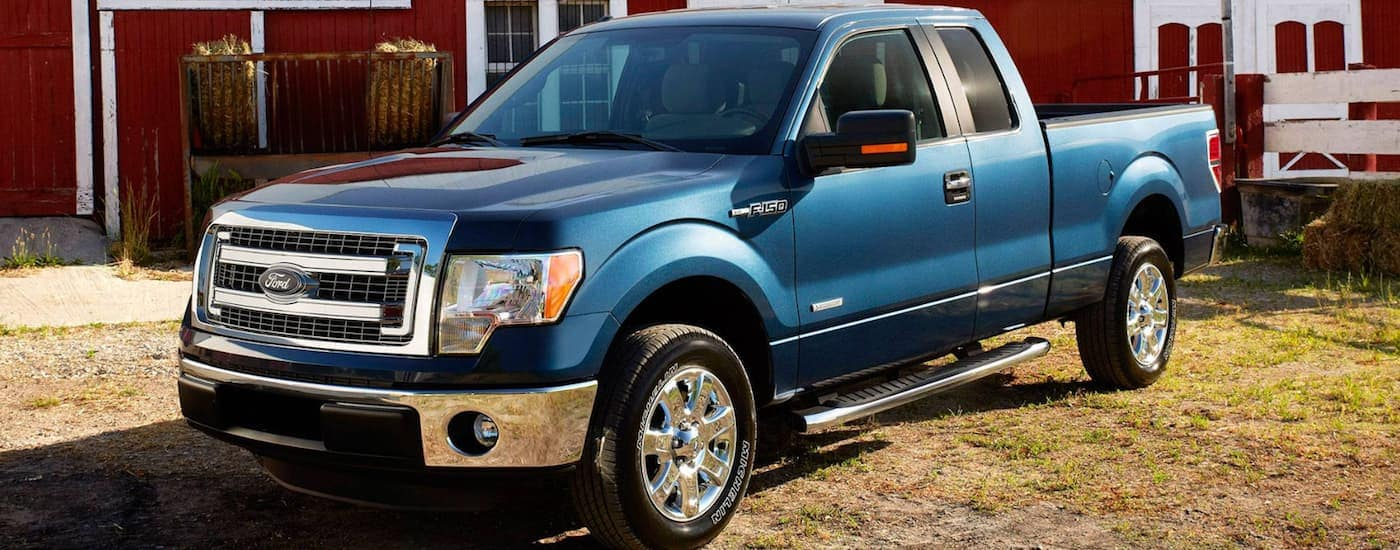 A blue 2014 Ford F-150 is parked in front of a red barn.