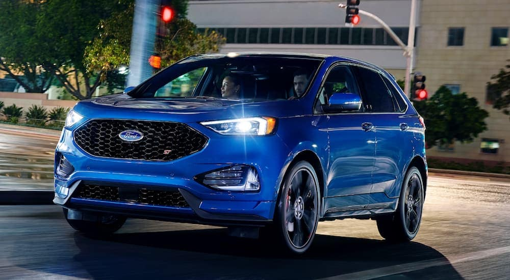 A blue 2020 Ford Edge is driving on a city street near Cincinnati, OH, at night.