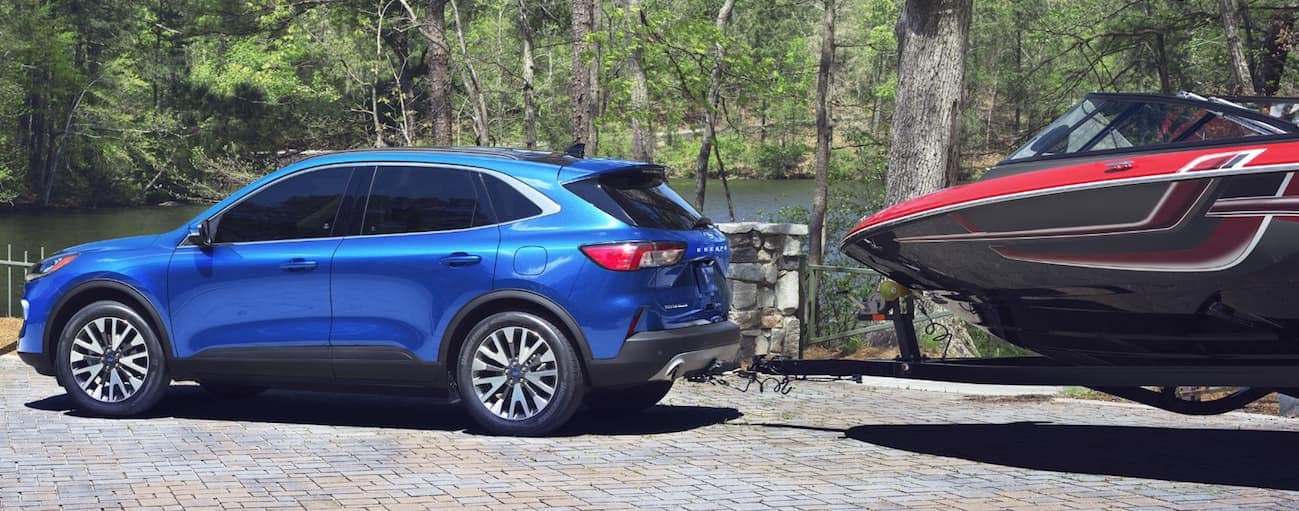 A blue 2020 Ford Escape is towing a large boat next a lake near Cincinnati, OH.