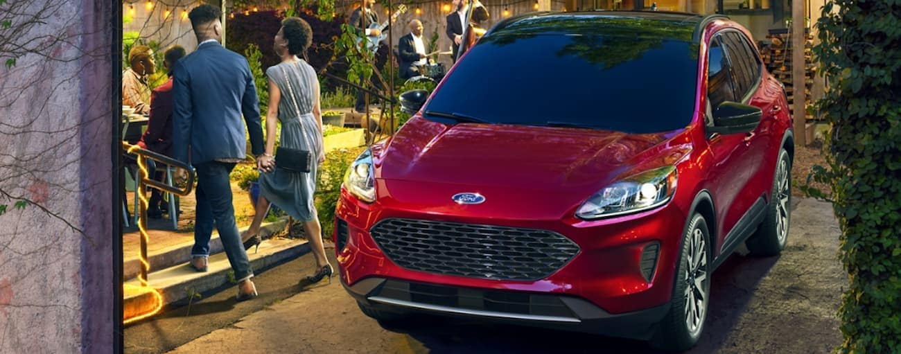 A red 2020 Ford Escape, which wins when comparing the 2020 Ford Escape vs 2020 Nissan Rogue, is parked next to a lit up garden near Cincinnati, OH.