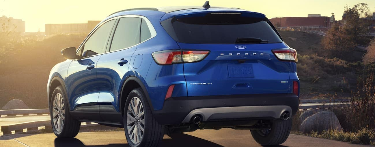 A blue 2020 Ford Escape is parked at a park while facing the sunset.