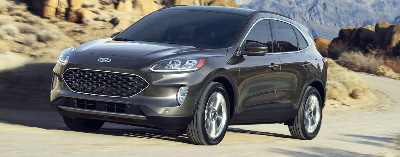A grey 2020 Ford Escape, which wins when comparing the 2020 Ford Escape vs 2020 Toyota RAV4 in Cincinnati, OH, is driving up a dirt hill.