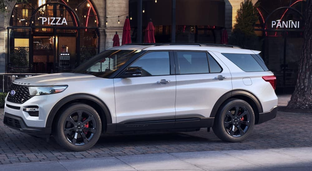 A side view of a gas model 2020 Ford Explorer that's parked in front of a pizza shop is shown.