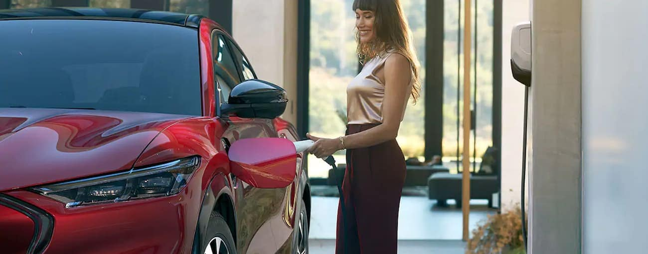 A woman is smiling while charging her 2021 Mach-E.