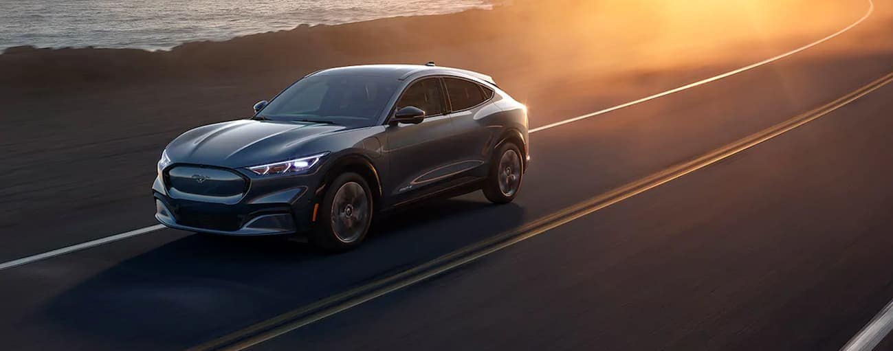 A grey 2021 Ford Mustang Mach-E, which wins when comparing the 2021 Ford Mustang Mach-E vs Tesla Model Y, is driving next to a lake near Cincinnati, OH, at sunset.