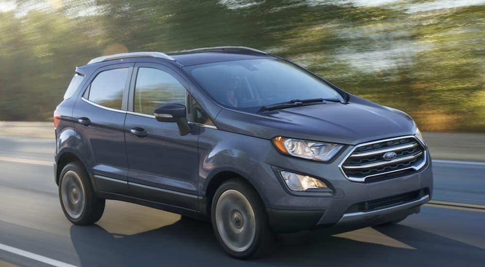 A blue 2020 Ford Ecosport is driving on a treelined road near Cincinnati, OH.