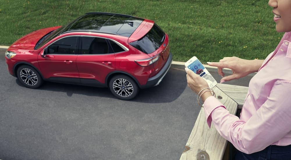 A woman is holding her phone while standing on her home's porch and connecting her 2020 Ford Escape to her WiFi Hotspot.