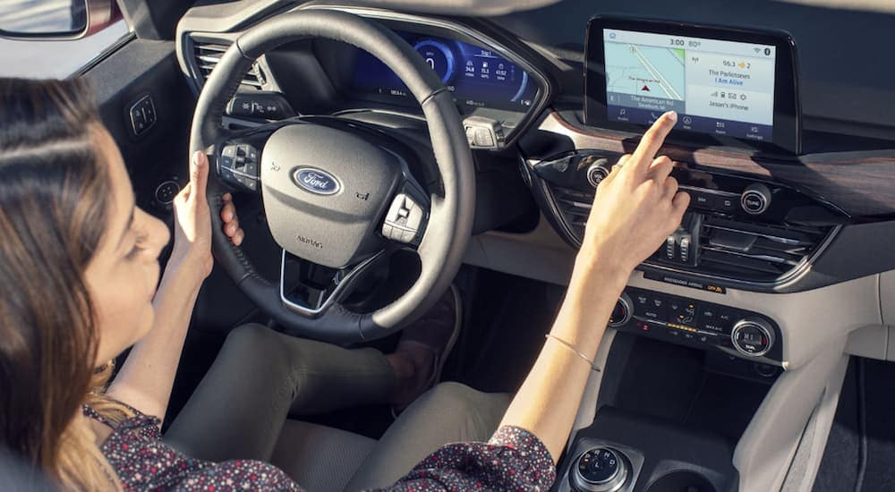 A birds eye view of a woman sitting in her 2020 Ford Escape, which is a popular option among Ford SUVs, while using the SYNC 3 on the infotainment system.