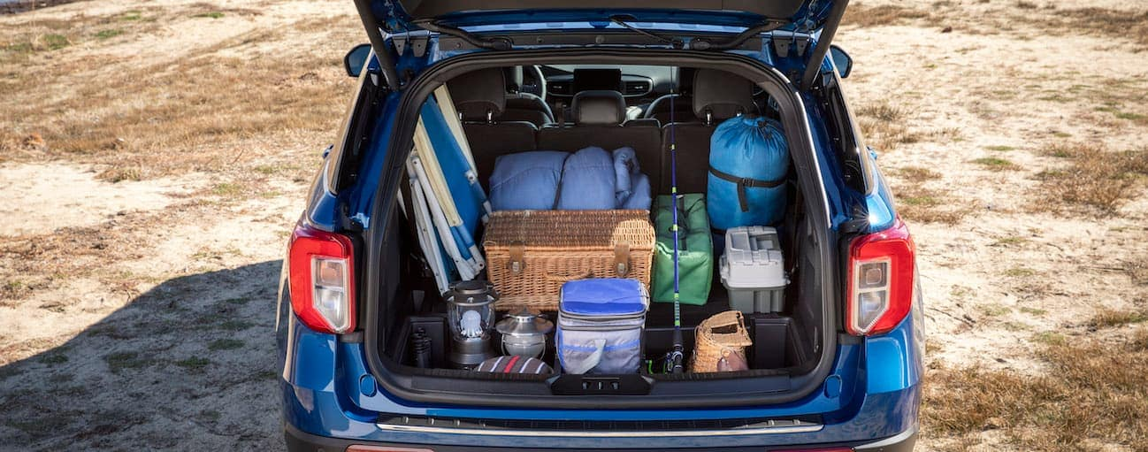 The liftgate of a 2020 Ford Explorer is open while the trunk is full of camping gear is shown.