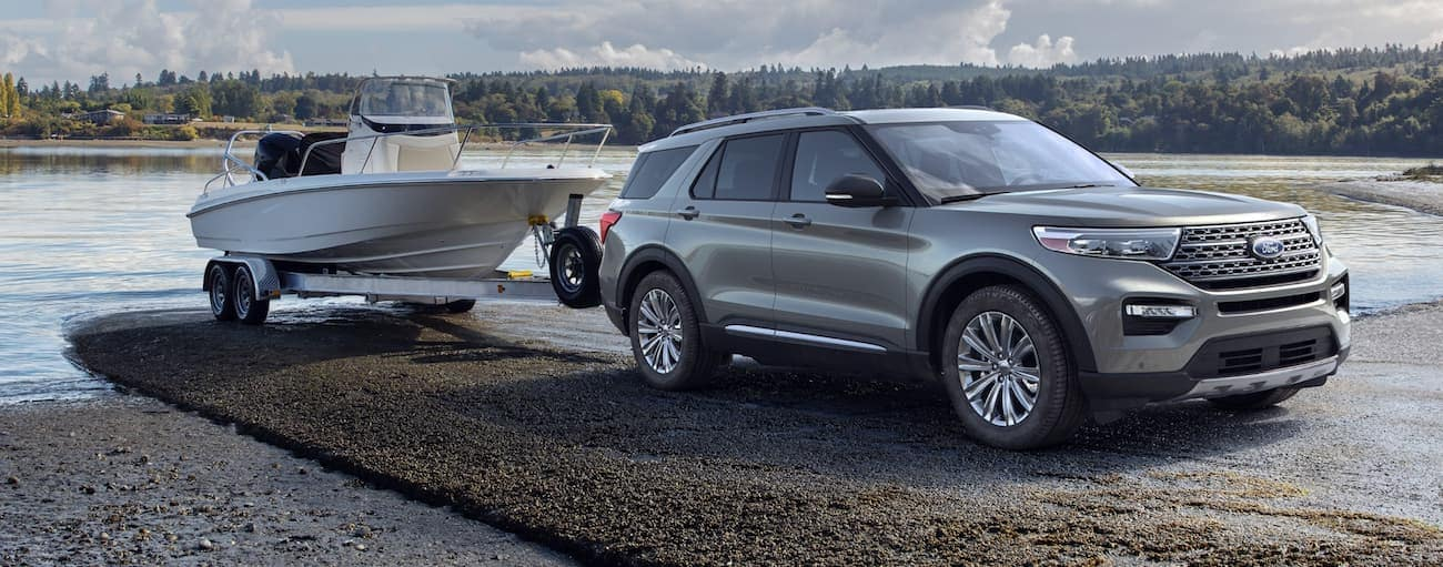 A silver 2020 Ford Explorer, which wins when comparing the 2020 Ford Explorer vs 2020 Chevy Traverse, is backing a large boat into a lake near Cincinnati, OH.